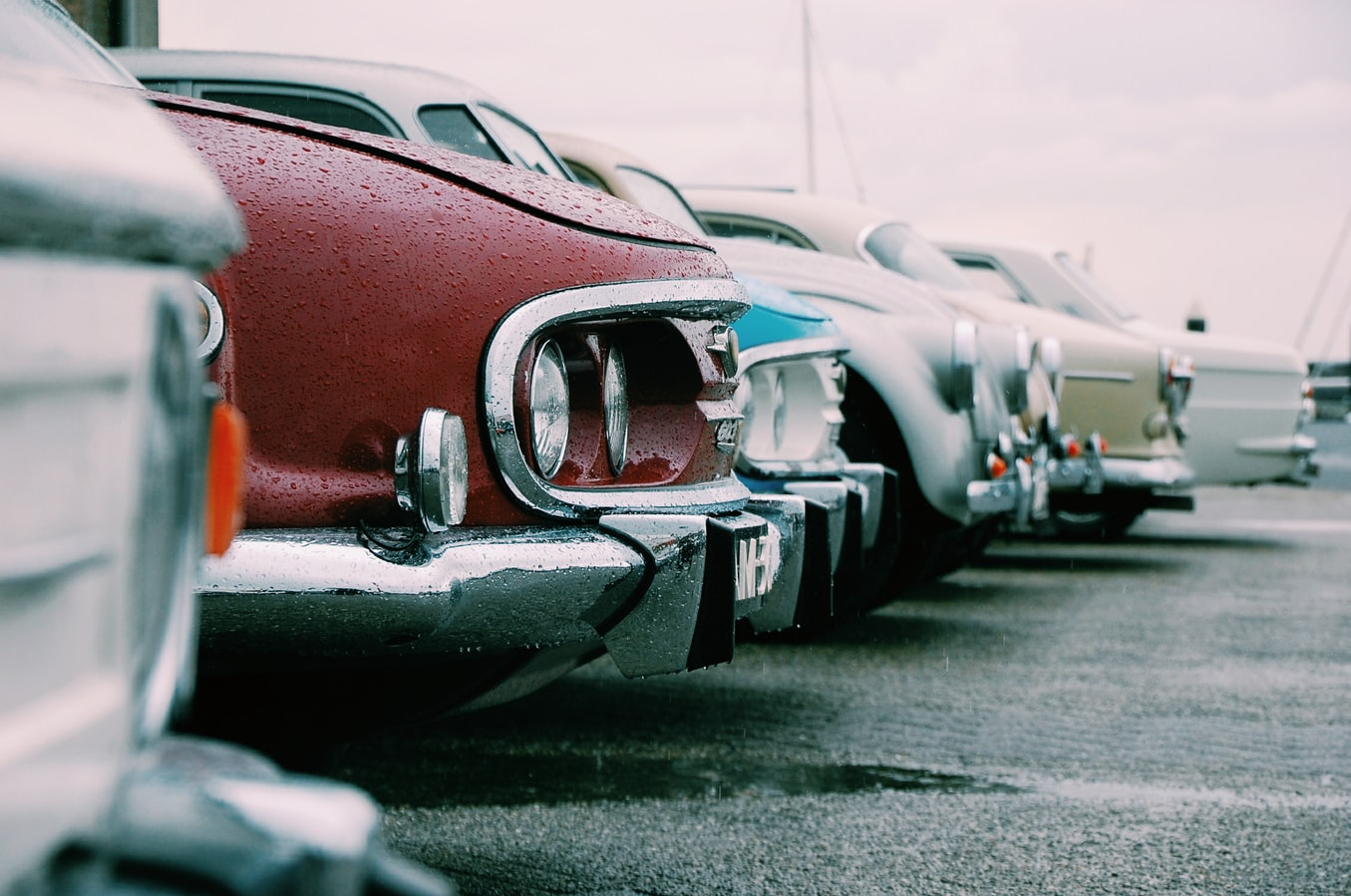 A close-up of the noses of several classic cars lined up in a parking lot