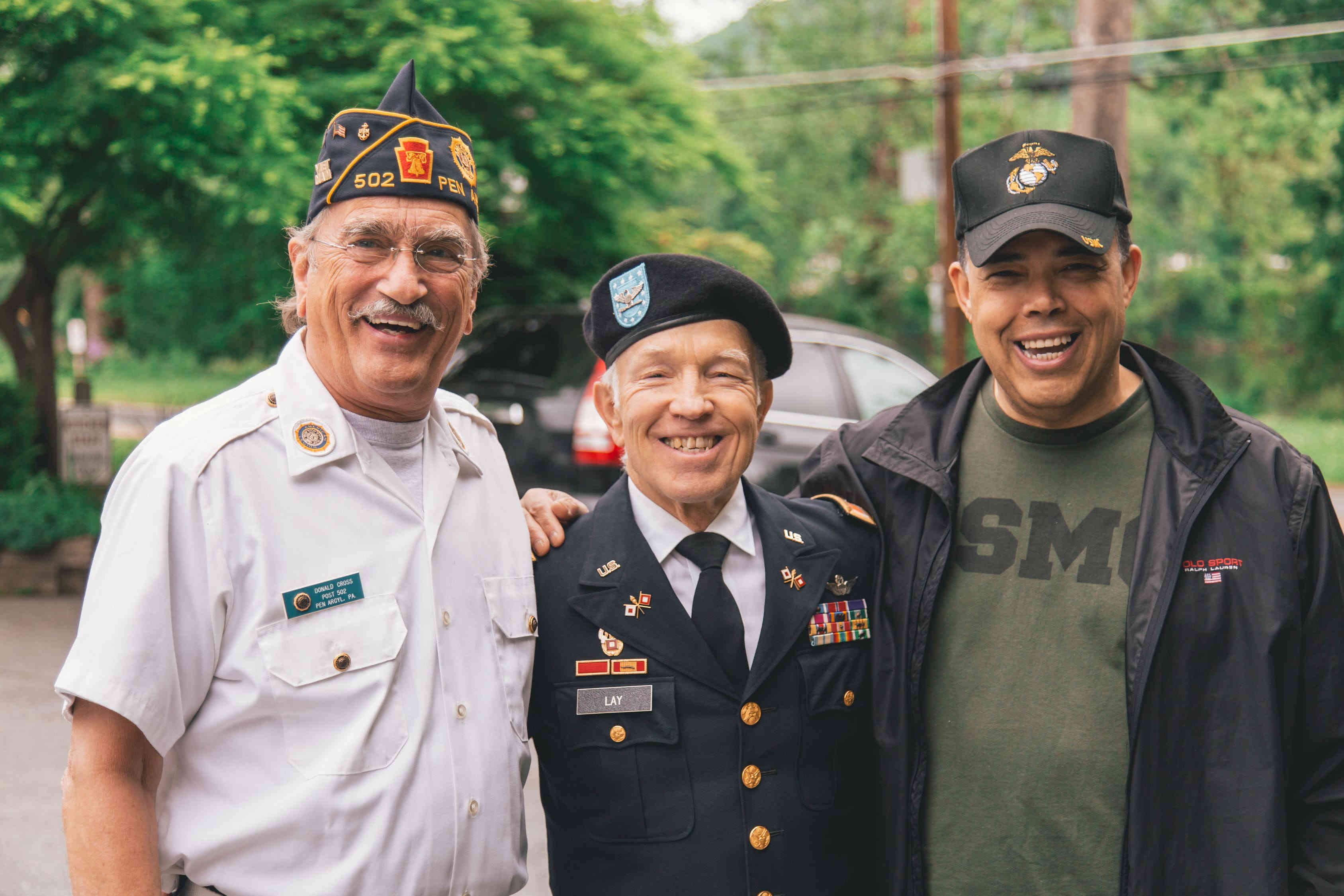An image of three veterans standing together and smiling.